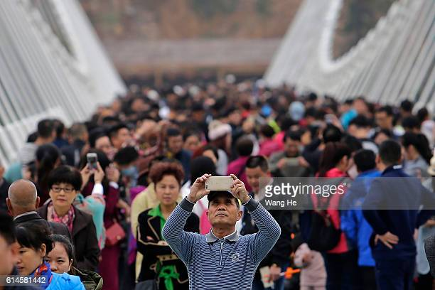A grandmother takes a picture of her grandson on the glassfloor suspension bridge in Zhangjiajie in south China's Hunan province on October 14 2016...