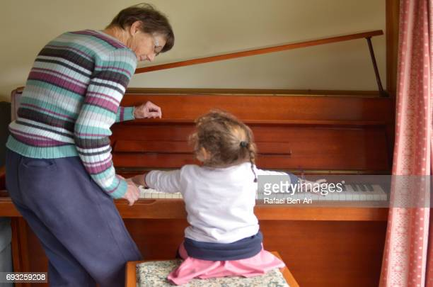 grandmother teaches her granddaughter to play piano - rafael ben ari stock pictures, royalty-free photos & images