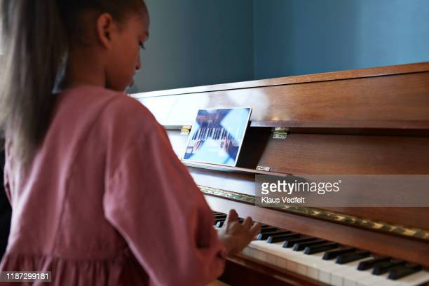 grandmother teaching grand piano to granddaughter - practicing stock pictures, royalty-free photos & images