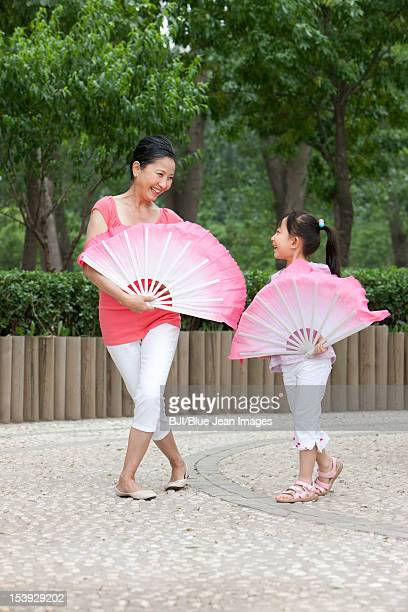 Grandmother teaching granddaughter fan dance
