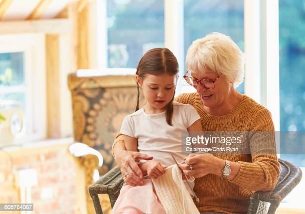 Grandmother teaching granddaughter knitting