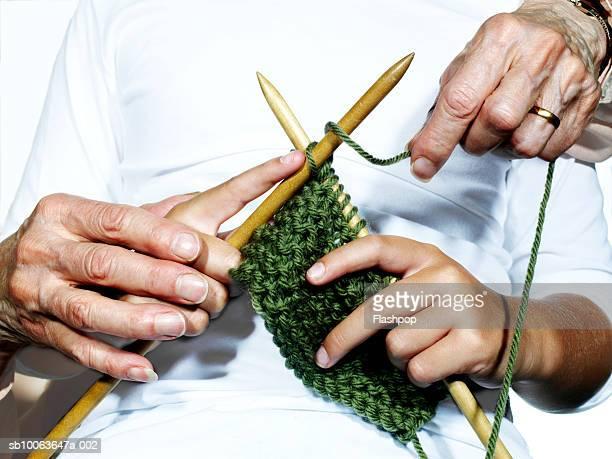 grandmother teaching granddaughter (8-9) to knit, close-up - stricken stock-fotos und bilder