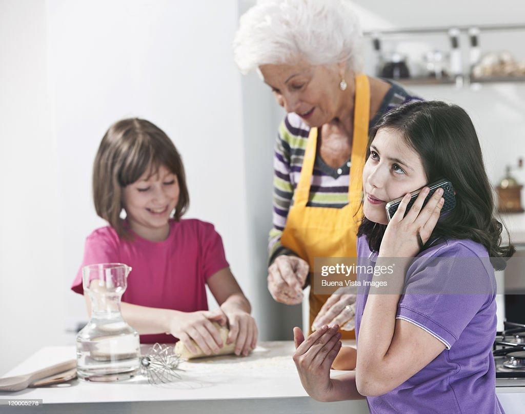 Grandmother teaching granddaughter to make pasta : Foto de stock