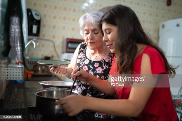 grandmother teaching her granddaughter how to cook - grandmother stock pictures, royalty-free photos & images