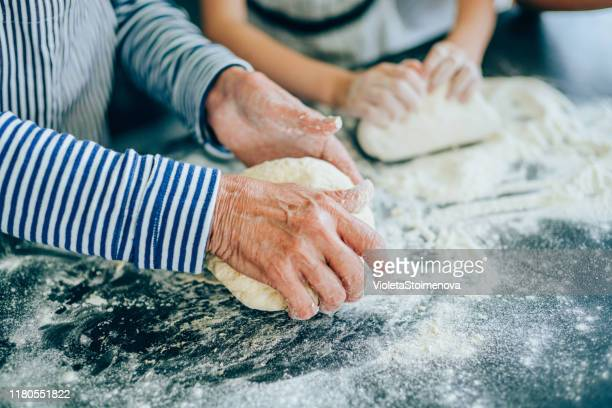 grandmother teaching her granddaughter to make cookies - tradition stock pictures, royalty-free photos & images