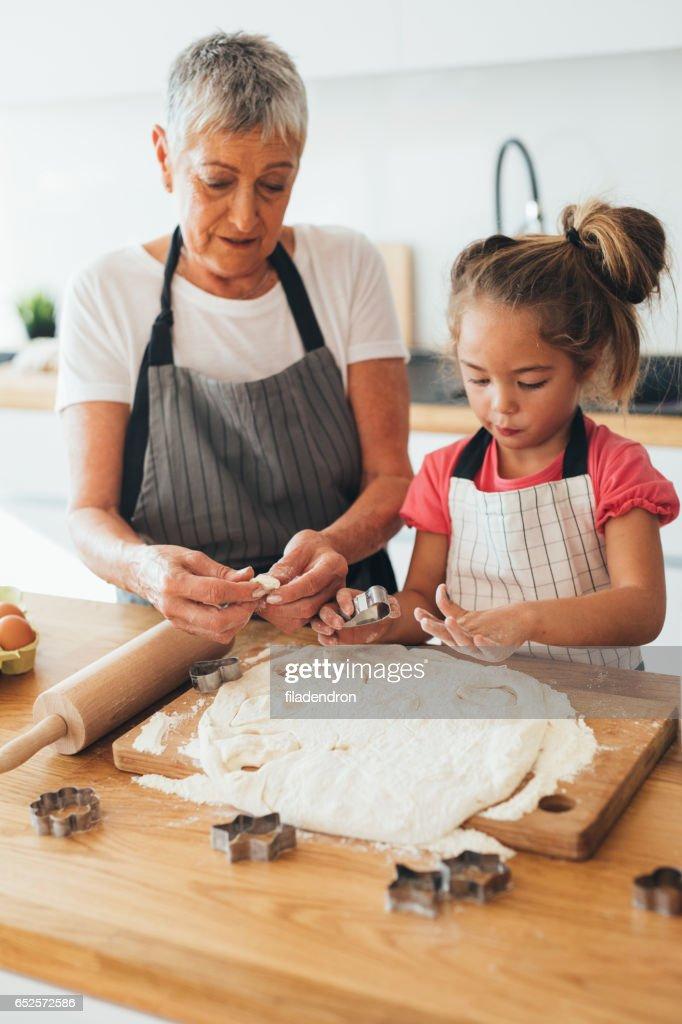 Farmor undervisning dotterdottern att göra cookies : Bildbanksbilder