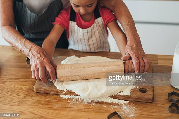 Grandmother teaching her granddaughter to roll out dough