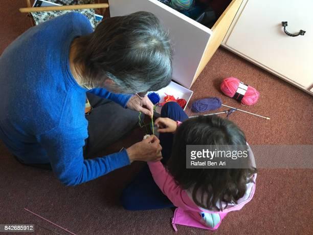 grandmother teaching her granddaugther to sew - rafael ben ari stock pictures, royalty-free photos & images