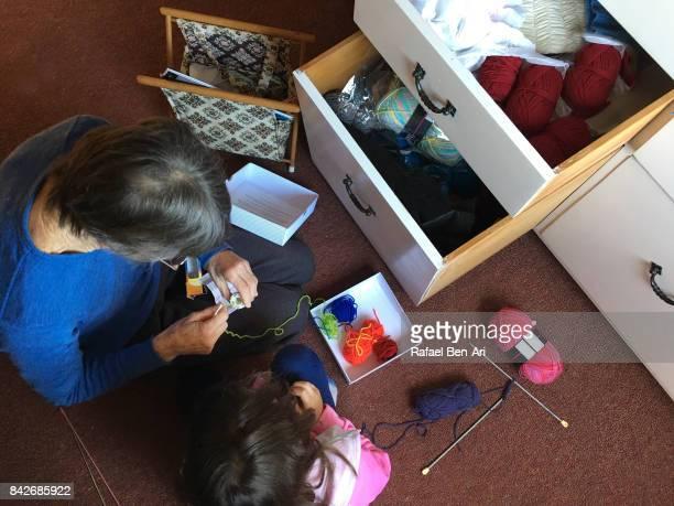grandmother teaching her granddaugther to sew - rafael ben ari stock-fotos und bilder