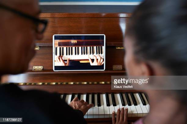 grandmother teaching piano to grandchild - distance learning stock pictures, royalty-free photos & images