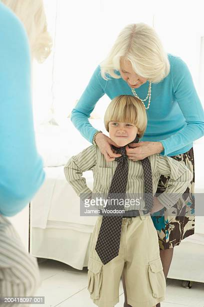Grandmother tying tie on grandson (4-6) in front of mirror,