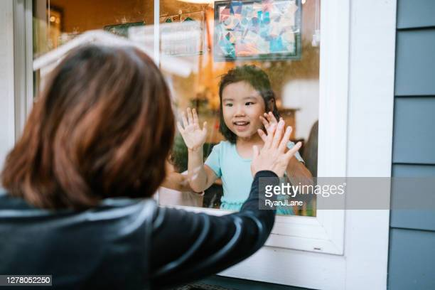 grandmother visits grandchildren through window - photographed through window stock pictures, royalty-free photos & images
