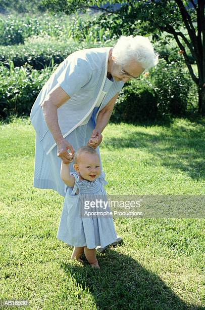 grandmother walking baby girl (9-12 months) in garden - great granddaughter stock photos and pictures