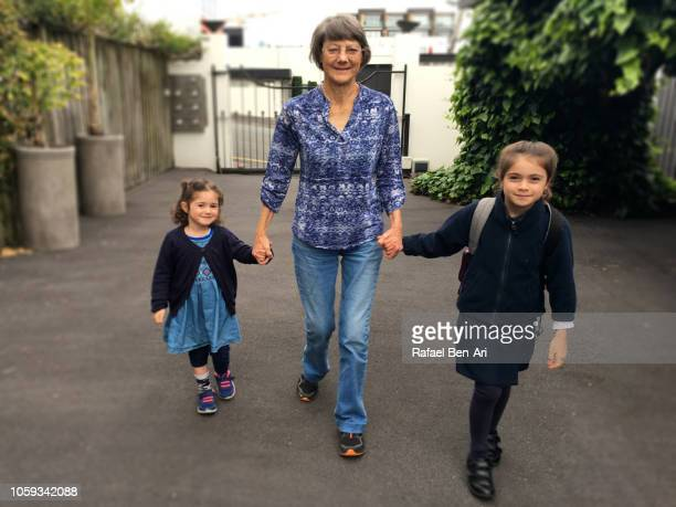 grandmother walking her granddaughters to school - rafael ben ari bildbanksfoton och bilder