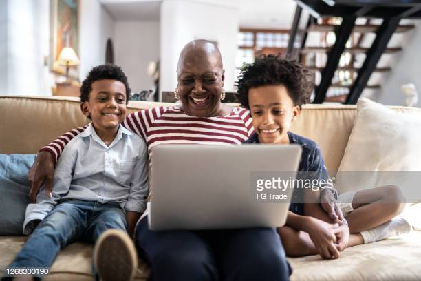 grandmother watching fun video on laptop with grandsons at home - watch what happens: live stock pictures, royalty-free photos & images