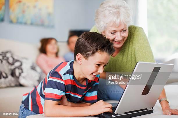 Grandmother watching grandson use laptop