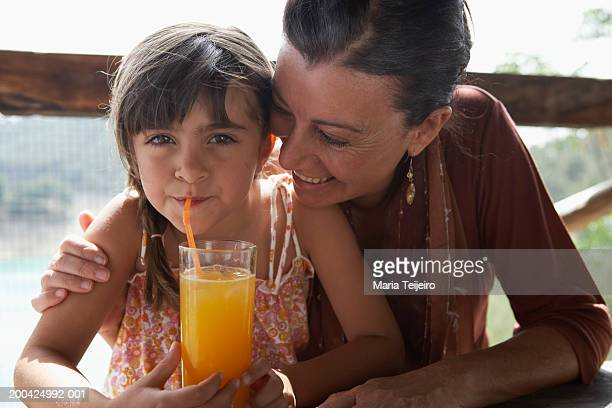 Grandmother with arm around girl (4-6) drinking from straw, portrait