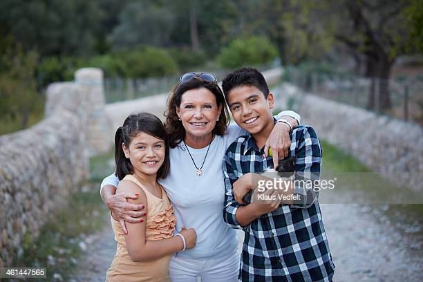 grandmother with arms around grandkids - klaus vedfelt mallorca stock pictures, royalty-free photos & images