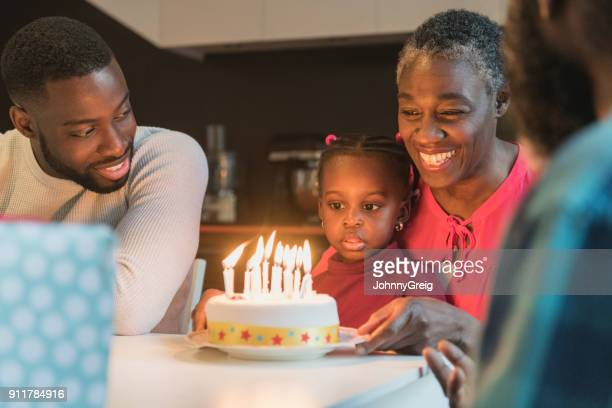 grandmother with birthday cake and granddaughter sitting on lap staring - british granny stock photos and pictures