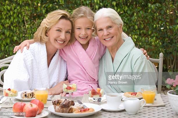 Grandmother with daughter and granddaughter having breakfast in garden, smiling, portrait