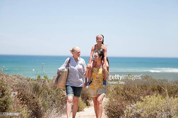 grandmother with daughter and granddaughter on beach path - woman carrying tote bag stock photos and pictures
