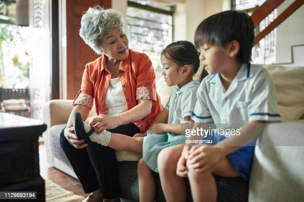 grandmother with grandchildren on sofa at home - generation gap stock pictures, royalty-free photos & images