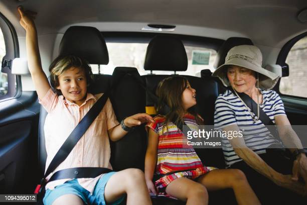 grandmother with grandchildren traveling in taxi - family inside car stock photos and pictures
