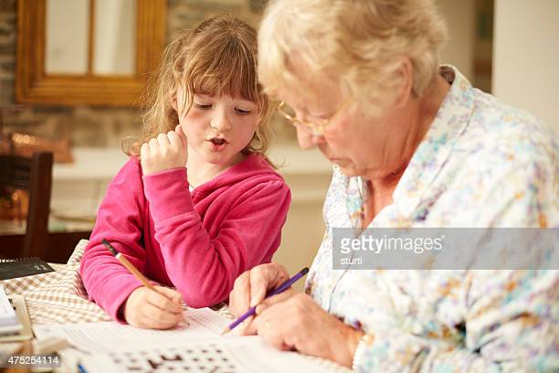 grandmother with granddaughter doig a crossword
