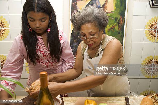 grandmother with granddaughter (10-12) in kitchen - west indies stock pictures, royalty-free photos & images