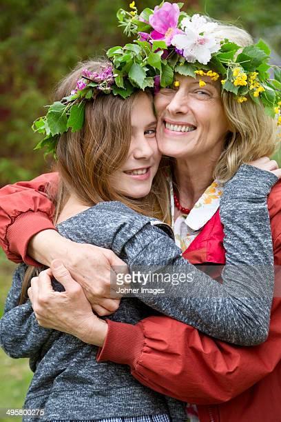 Grandmother with granddaughter wearing flower wreaths, Nykoping, Sodermanland, Sweden