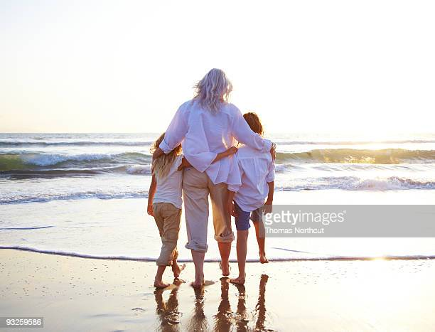 grandmother with granddaughters at the beach. - beautiful granny stock photos and pictures