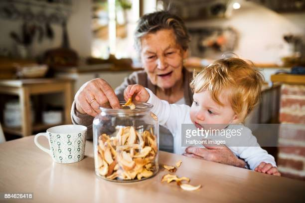 Grandmother with grandson at home storing dried apples.