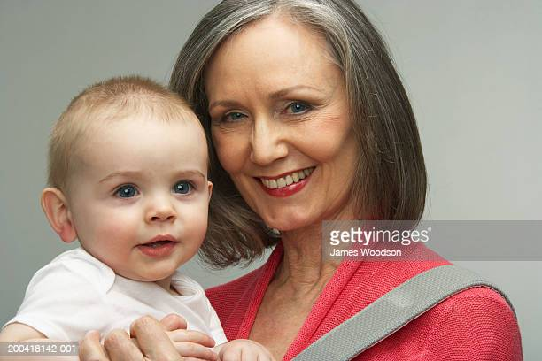 Grandmother with grandson (9-12 months) in baby carrier, smiling,