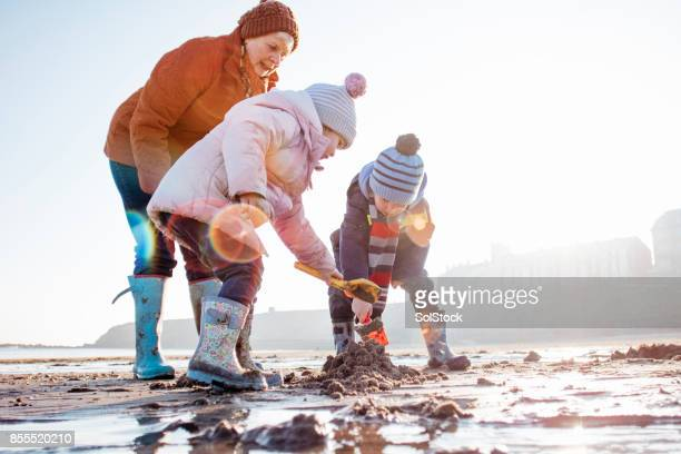 Grandmother with her Grandchildren Digging in the Sand