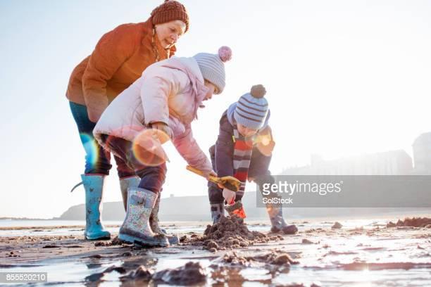 Oma mit ihrem Enkel Graben im Sand