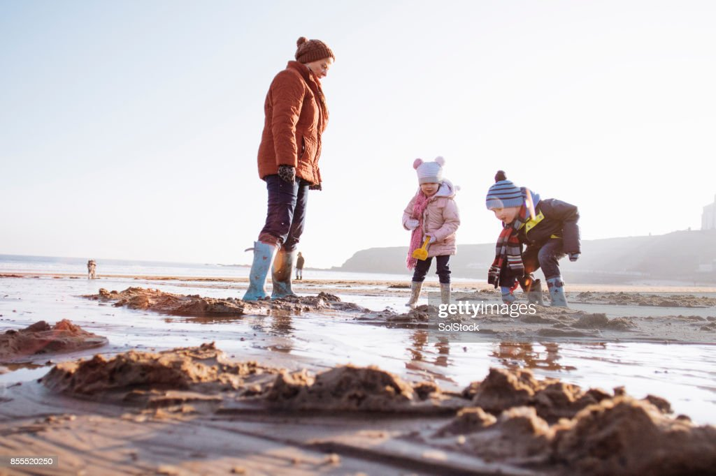 Grandmother with her Grandchildren on the Beach : Stock Photo