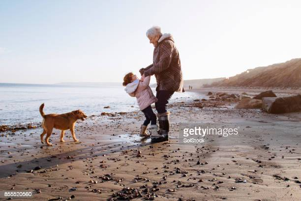 grandmother with her granddaughter on the beach - cumbria stock pictures, royalty-free photos & images