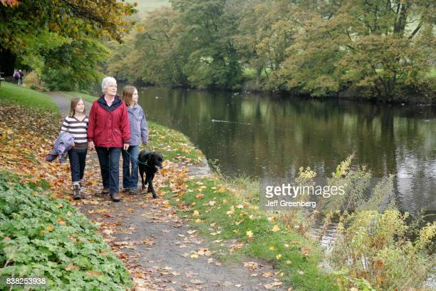A grandmother with her granddaughters walking her dog by the River Whafe in Burnsall