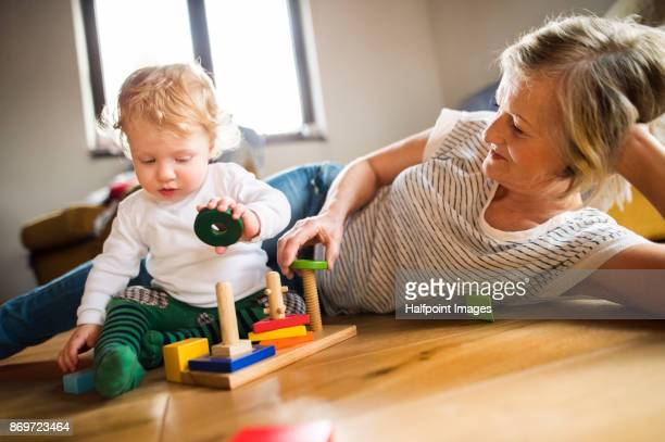 Grandmother with her grandson at home playing with toys.