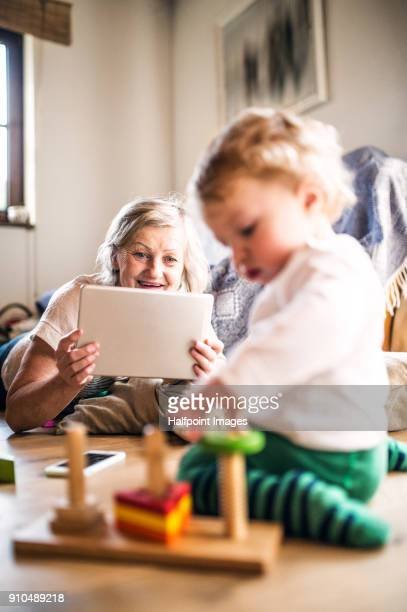 Grandmother with her grandson at home using tablet.