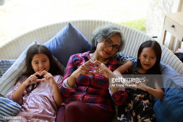 grandmother with her two grandchildren, asian family,looking at camera, showing love sign - moment of silence stock pictures, royalty-free photos & images