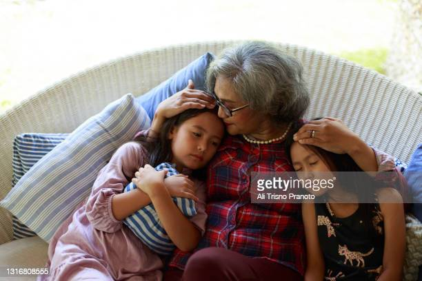 grandmother with her two grandchildren, asian family,relaxing and sleeping in sofa - moment of silence stock pictures, royalty-free photos & images