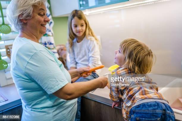 Grand-mère avec des enfants dans la cuisine à préparer des légumes pour le déjeuner