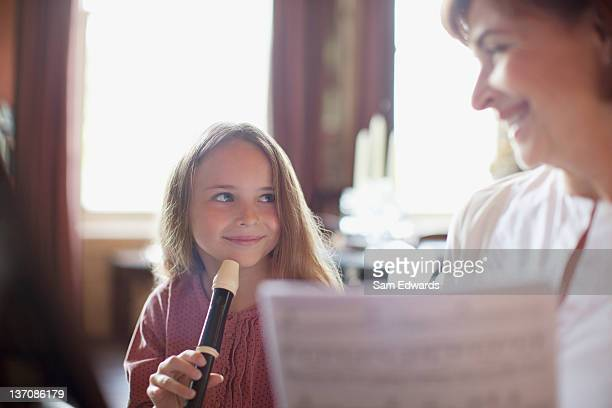 grandmother with sheet music watching granddaughter practice on recorder - recorder musical instrument stock photos and pictures