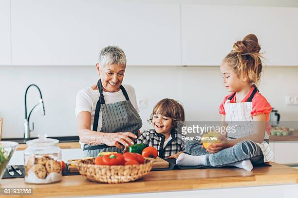 Grandmother with two small children in the kitchen