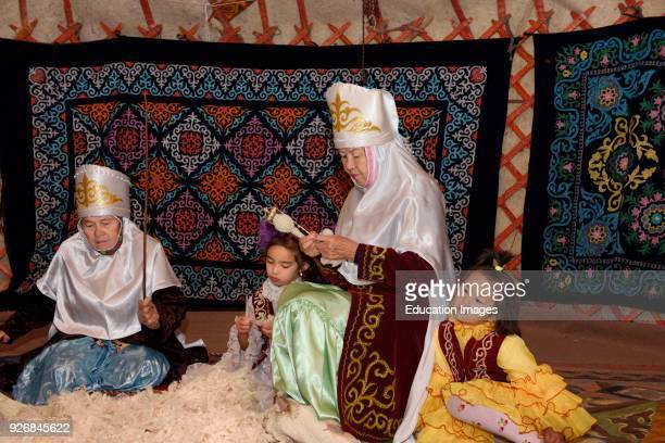 Grandmothers and children in a yurt beating and spinning wool Huns village Kazakhstan