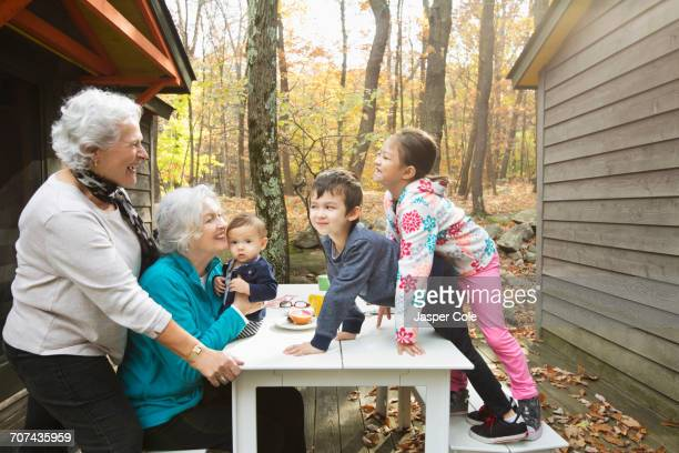 Grandmothers playing with grandchildren at breakfast table outdoors