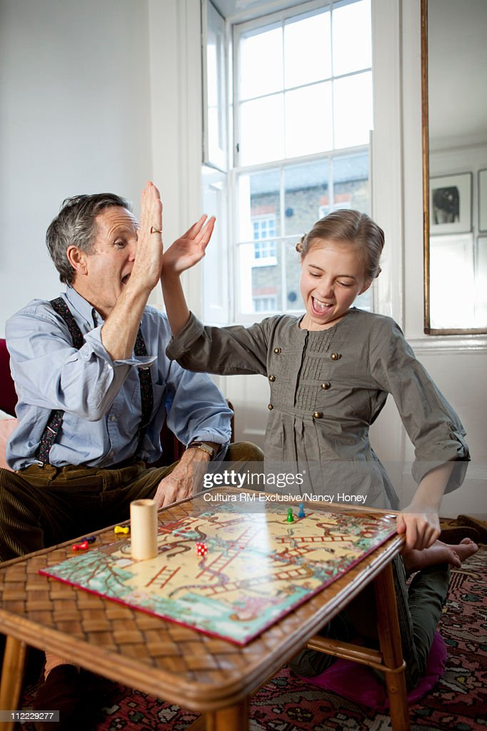 Grandpa and girl playing game and doing a hi-five : Stock-Foto