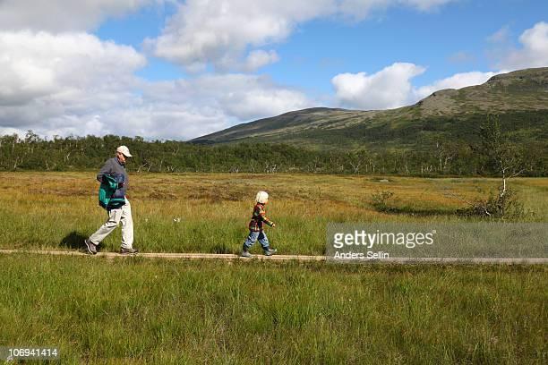 Grandpa and grandchild walking trail in mountain