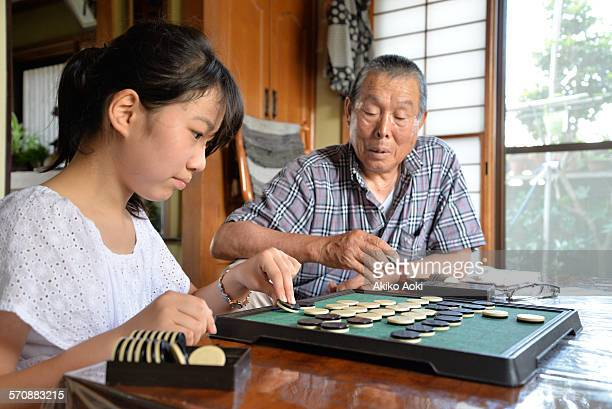 Grandpa and granddaughter playing Othello game.
